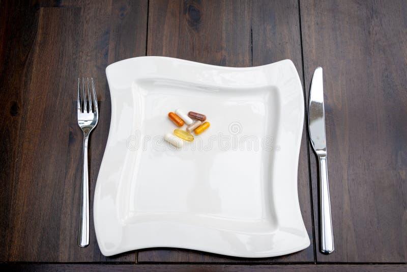 Olika piller är på vita plattor på en brun tabell royaltyfria bilder