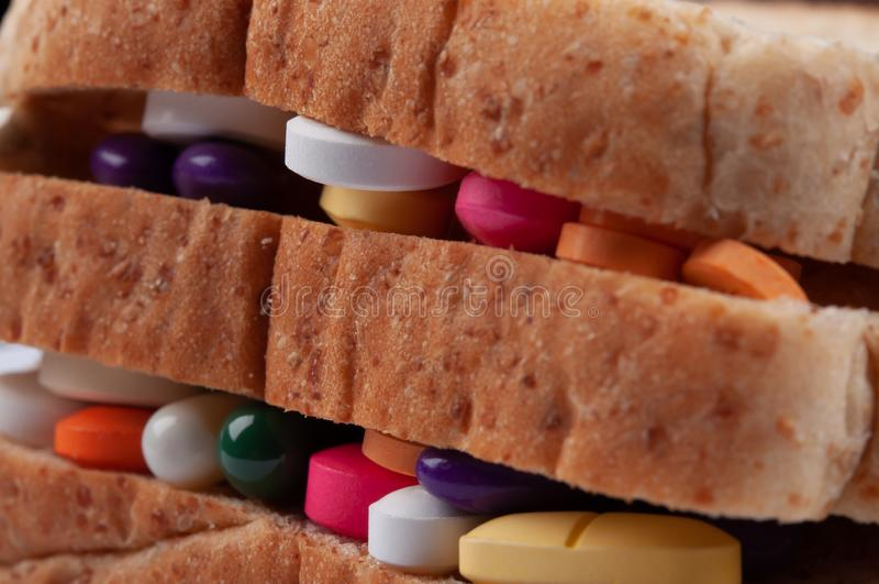 Olika piller, minnestavlor och kapslar av medicin som fyller i brödsmörgåslager; mat påverkar hälsa som medicinconcep arkivfoto