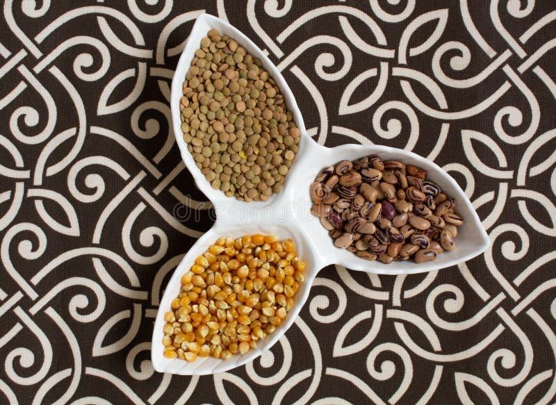 Olika sädesslag, sädesslag Olika typer av grus i koppar på en mönstrad bakgrund Havre bönor äta som är sunt arkivbild