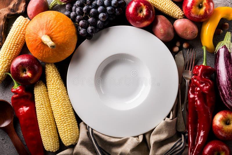 Olika säsongsbetonade höstgrönsaker och frukter med den tomma plattan royaltyfria foton