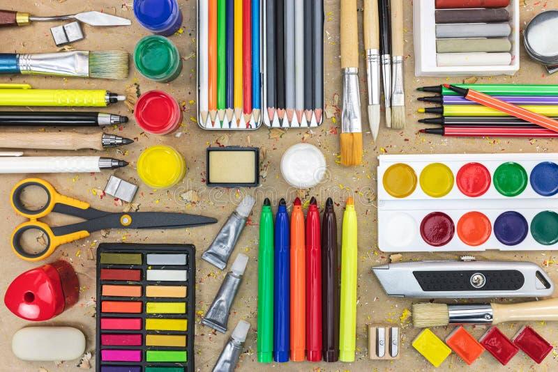 Olika skolatillförsel på skrivbordet kulöra blyertspennor, markörer, pai arkivbild