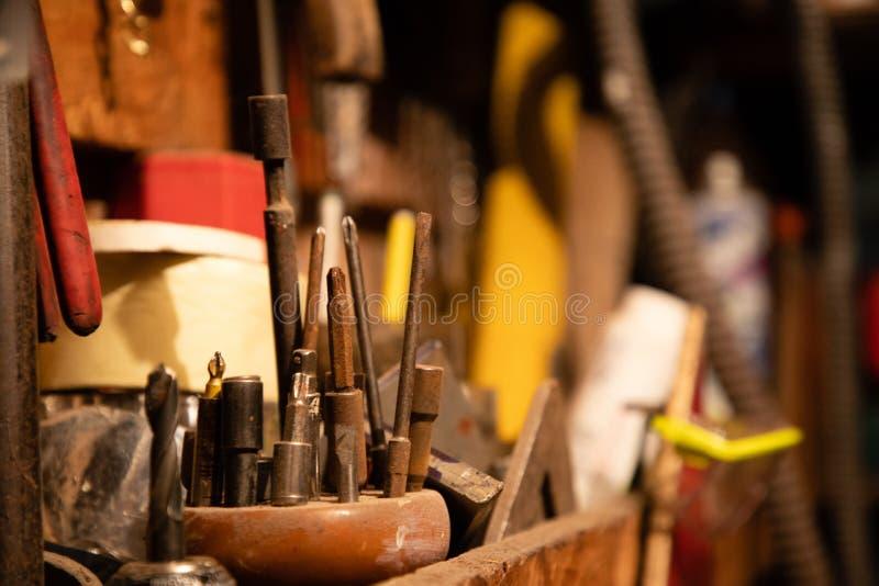 Olika skruvmejslar och andra hjälpmedel på garage arkivbild