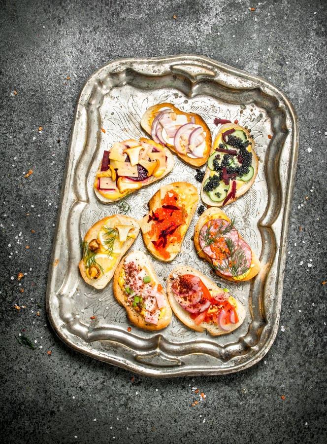 Olika smörgåsar med den röda kaviaren, bacon, ost och nya grönsaker på ett stålmagasin arkivbild