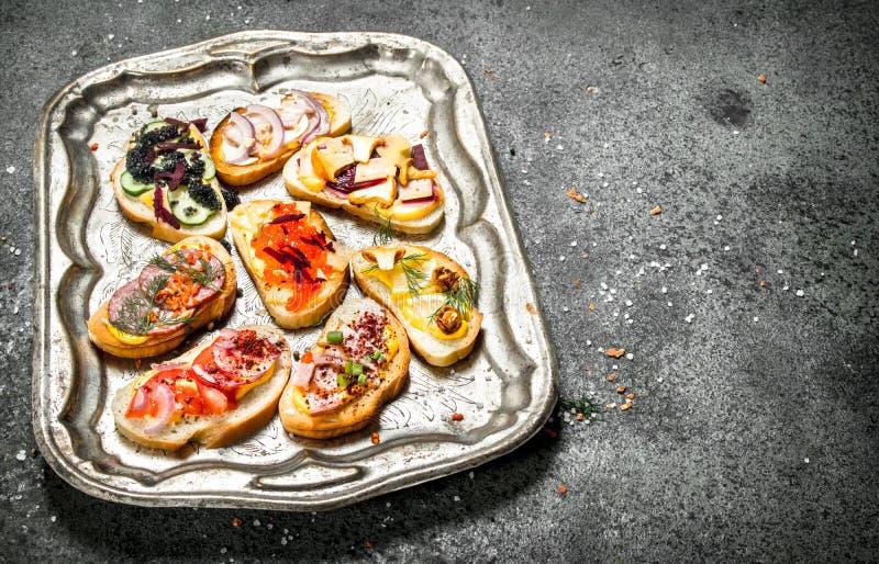 Olika smörgåsar med den röda kaviaren, bacon, ost och nya grönsaker på ett stålmagasin arkivfoton