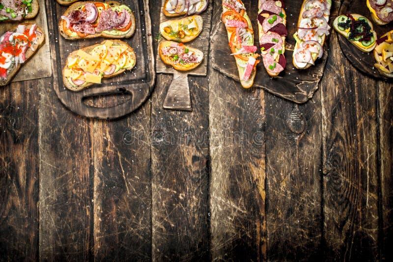 Olika smörgåsar med skaldjur, kött och grönsaker arkivbild