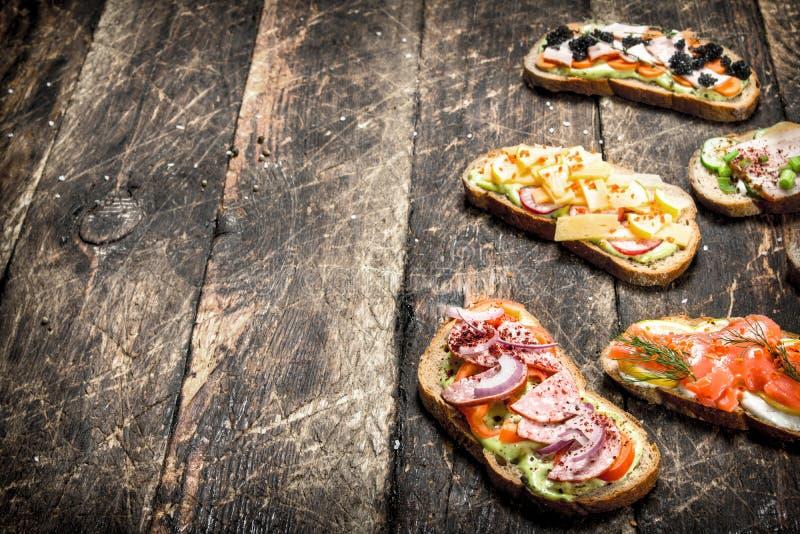 Olika smörgåsar med skaldjur, kött och grönsaker På en träbakgrund royaltyfri fotografi