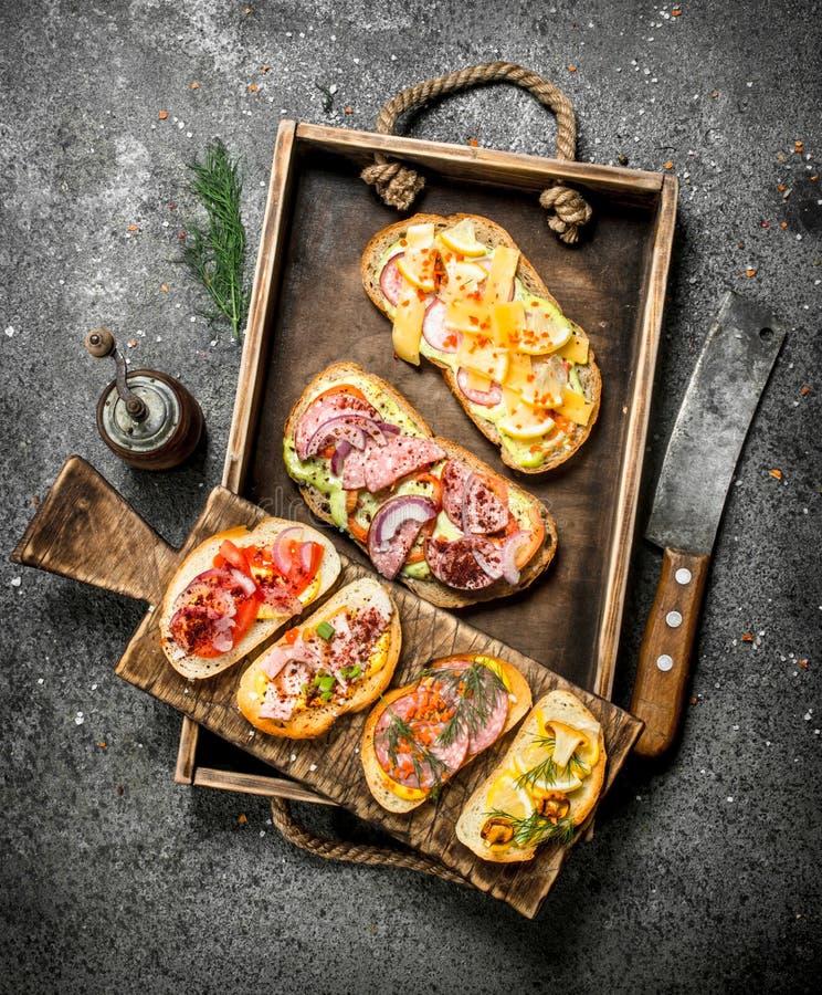 Olika smörgåsar med skaldjur, kött och grönsaker på ett gammalt magasin arkivbilder