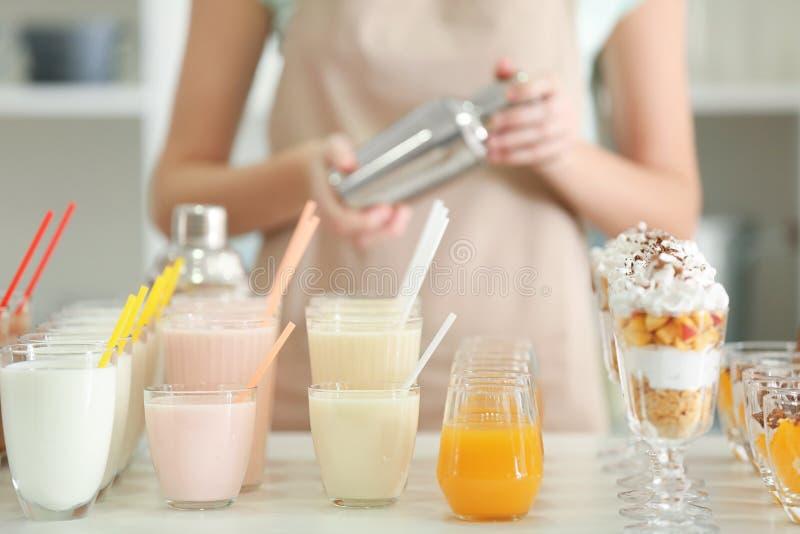 Olika smakliga milkshakar och kvinnlig bartender arkivfoto
