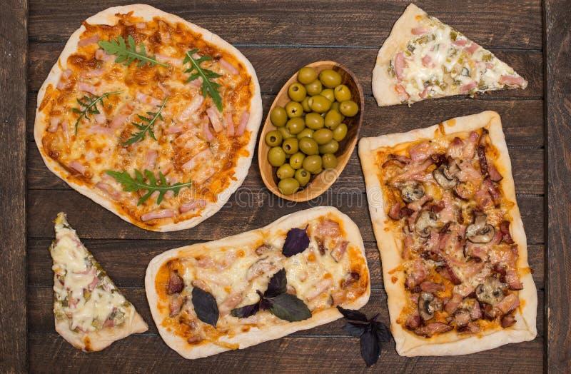 Olika sorter av liten pizza på lantlig sjaskig bakgrund Olik hemlagad pizza, matställeparti hemma, bästa sikt arkivbild