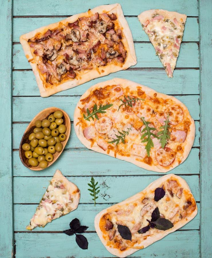 Olika sorter av liten pizza på lantlig sjaskig chic bakgrund Olik hemlagad pizza, matställeparti hemma, bästa sikt arkivbild