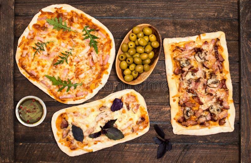 Olika sorter av liten pizza på lantlig träbakgrund Olik hemlagad pizza, matställeparti hemma, bästa sikt arkivbild