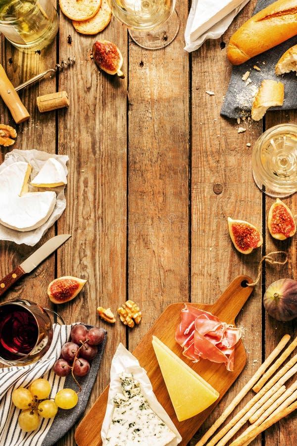 Olika sorter av ostar, vin, bagetter, frukter och mellanmål royaltyfri foto