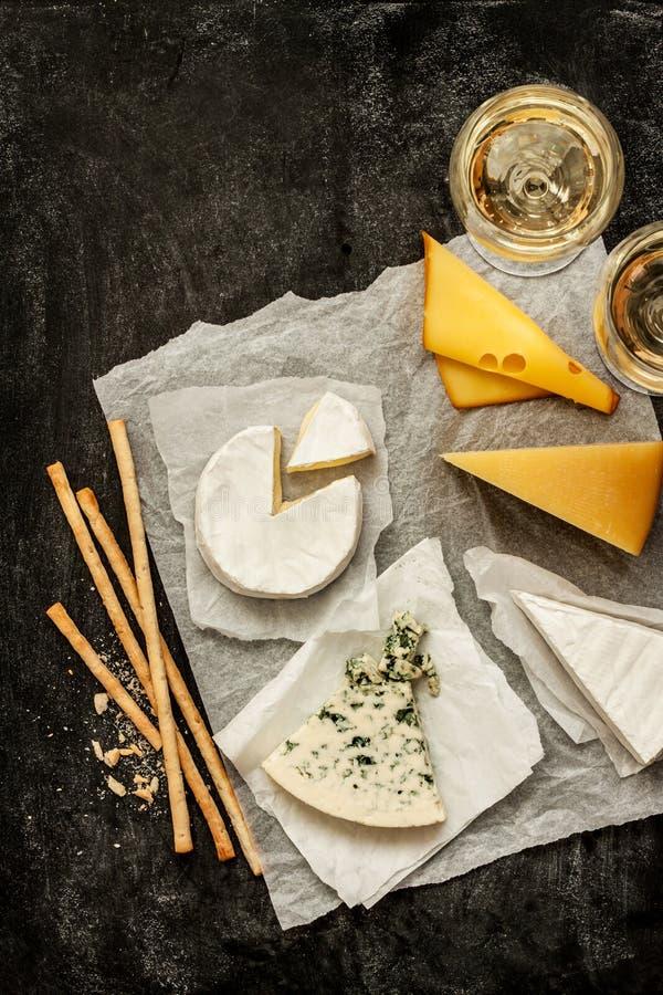 Olika sorter av ostar, vitt vin och mellanmål på svart arkivfoto