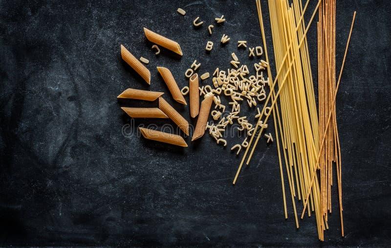 Olika sorter av pasta på den svarta svart tavlan fotografering för bildbyråer