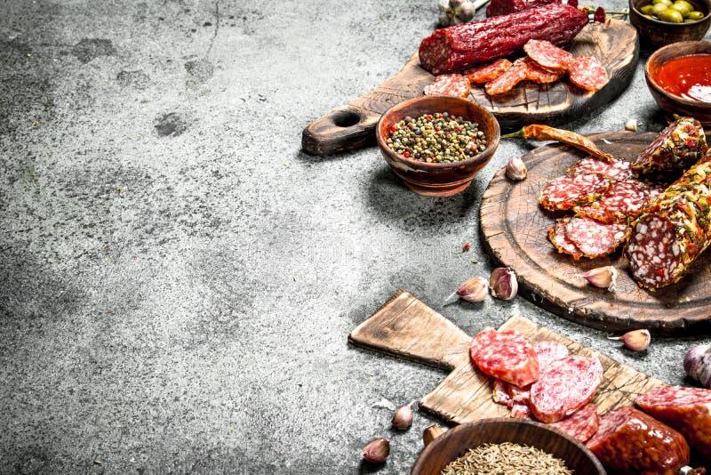 Olika sorter av salami med kryddor och örter på gamla bräden arkivfoto