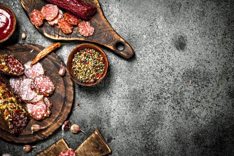 Olika sorter av salami med kryddor och örter på gamla bräden arkivbilder