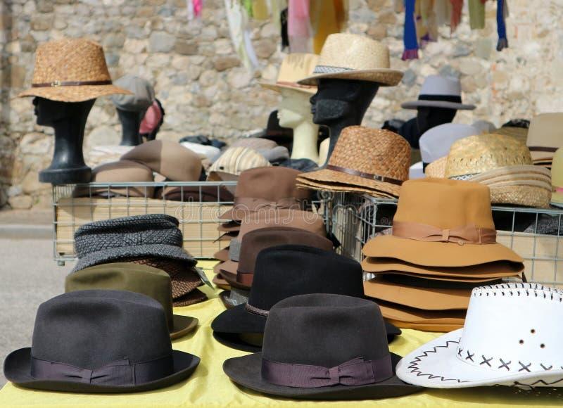 Olika stilmanhattar på en hylla av en gatamarknad På bakgrund dvärghuvud som bär sugrörhattar royaltyfri fotografi