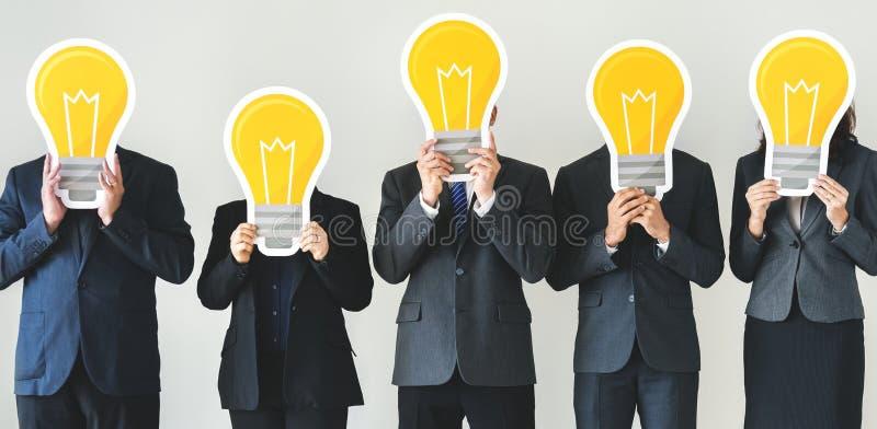 Olika symboler för lightbulb för affärsfolk hållande över framsidor arkivfoton