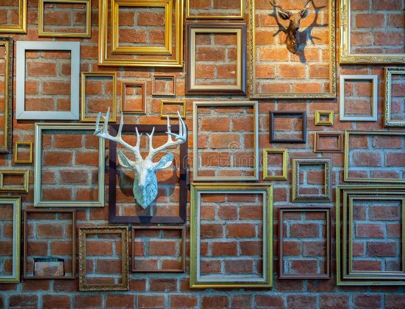 Olika tomma fotoramar med murbrukhjorthuvudet som hänger på tegelstenväggen arkivbilder