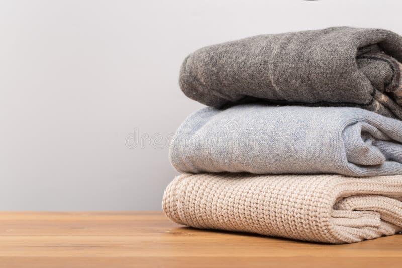 Olika tröjor på en trätabell på en ljus bakgrund Höst- och vinterkläder arkivfoton