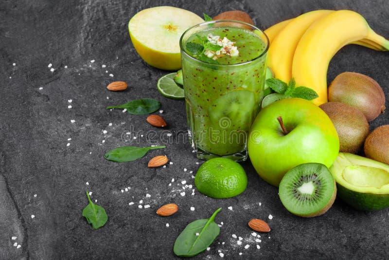 Olika tropiska frukter och grön smoothie från kiwin på ett mörker - grå bakgrund Näringsrika ingredienser arkivbilder