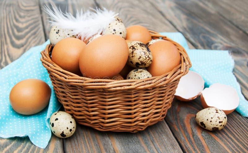 Olika typer av ägg i en korg arkivfoton