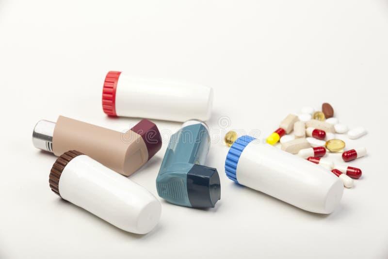 Olika typer av astmainhalatorer och några preventivpillerar på vit royaltyfri bild