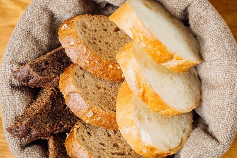 Olika typer av bröd i korgen på tabellen royaltyfria foton