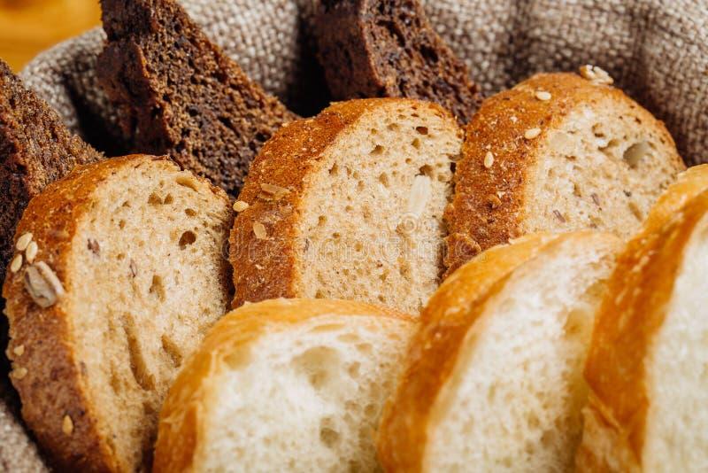 Olika typer av bröd i korgen på tabellen fotografering för bildbyråer