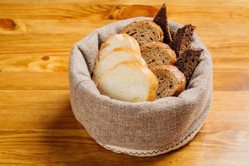 Olika typer av bröd i korgen på tabellen arkivfoto