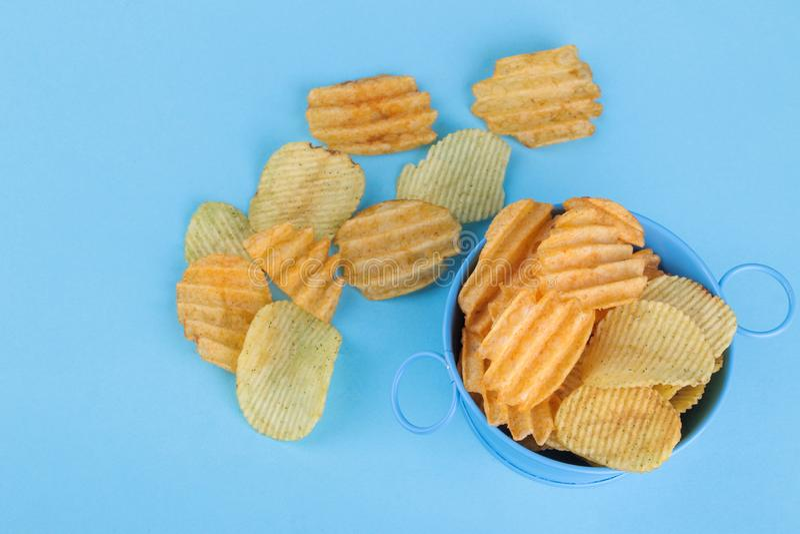 Olika typer av chiper i en blå bunke på en ljus blå bakgrund ovanför sikt royaltyfria bilder