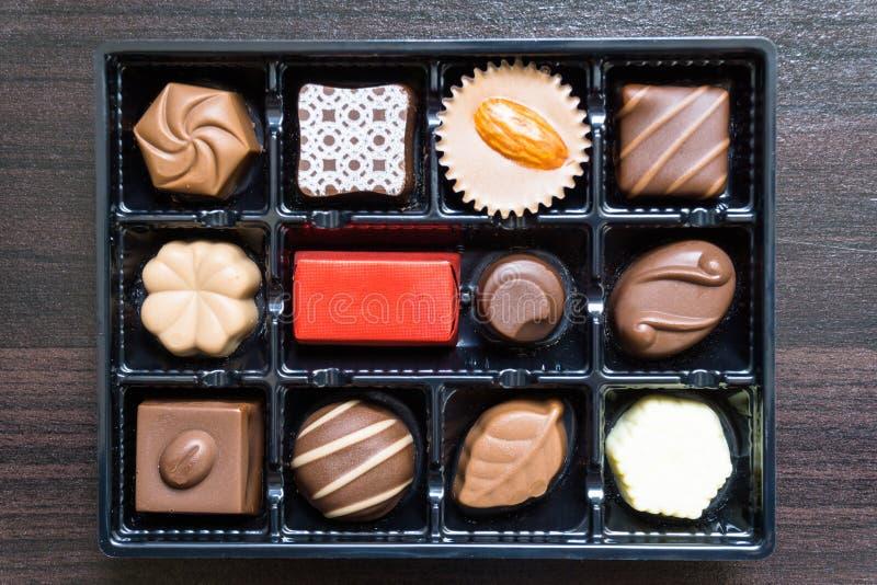 Olika typer av chokladgodisar på en träbakgrund/läckra chokladgodisar i gåvaask på tabellnärbild royaltyfri bild