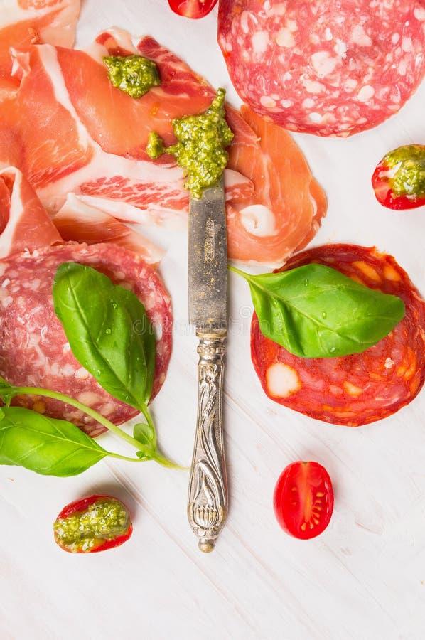 Olika typer av den italienska korven och skinka med den basilikapesto och kniven arkivfoton