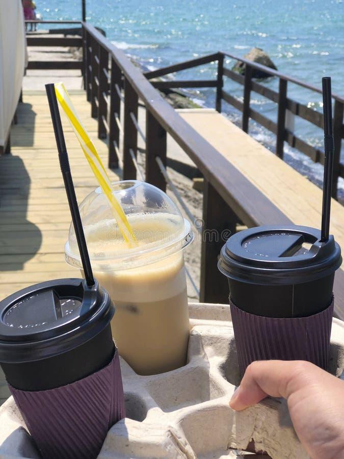 Olika typer av kaffe som går takeaway i händerna med bea royaltyfria foton