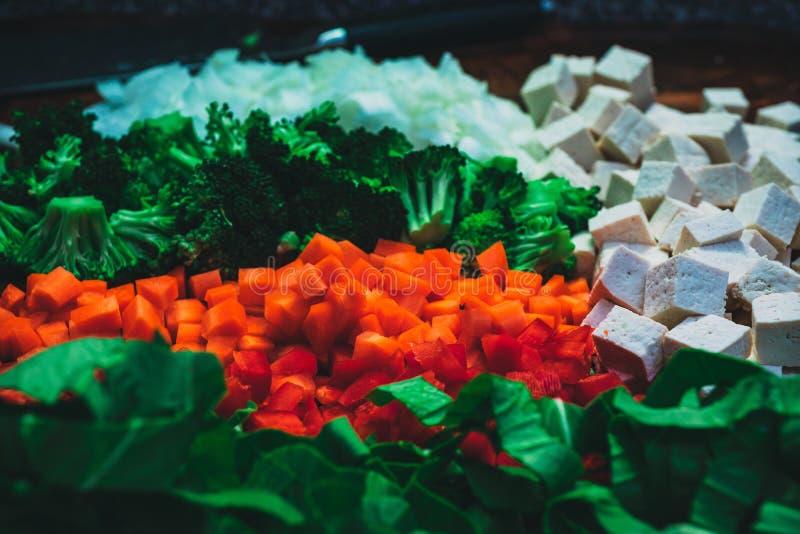 Olika typer av klippta grönsaker med kubikost på sidan royaltyfri fotografi