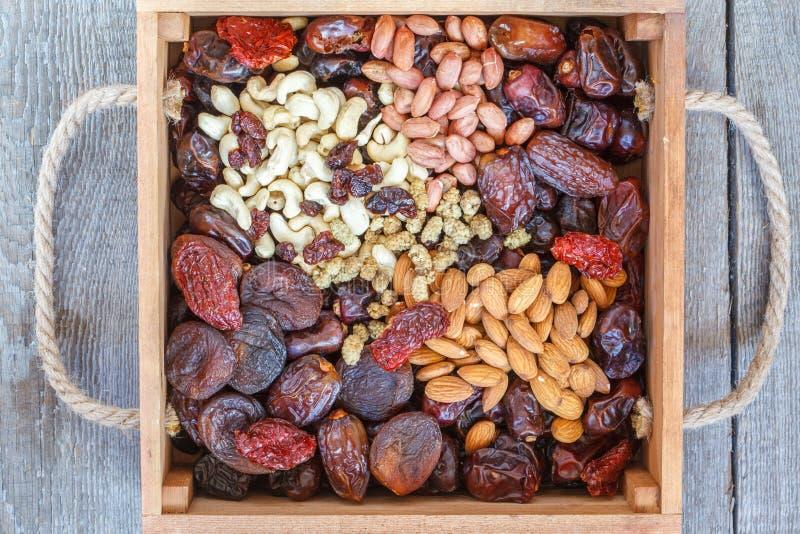 Olika typer av muttrar och torkade frukter i en träask royaltyfria foton