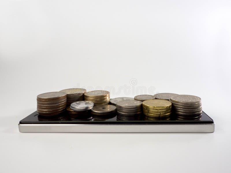 Olika typer av mynt på en mobiltelefon royaltyfria foton