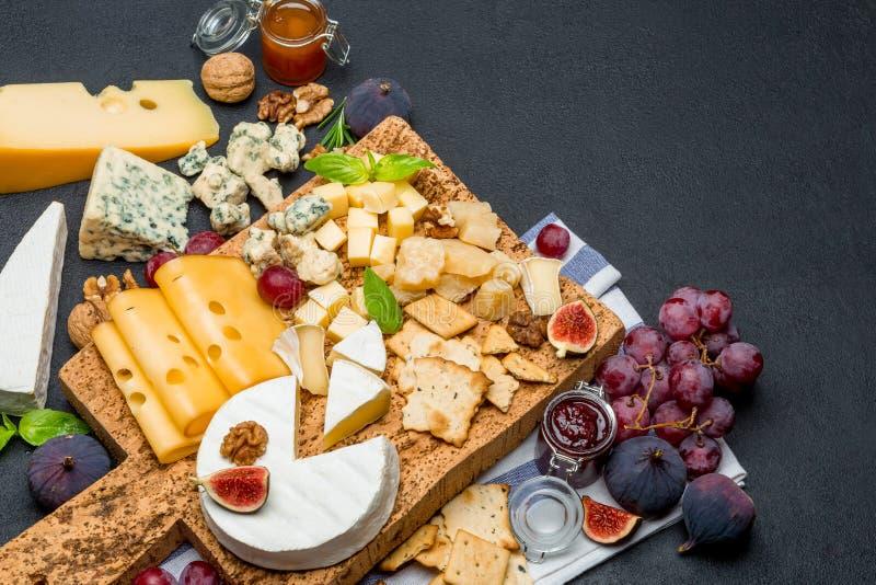 Olika typer av ost - brie, camembert, roquefort och cheddar på träbräde royaltyfri fotografi