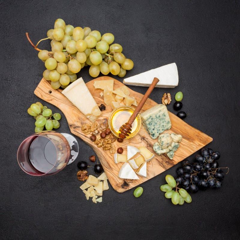 Olika typer av ost - brie, camembert, roquefort och cheddar och vin arkivfoton