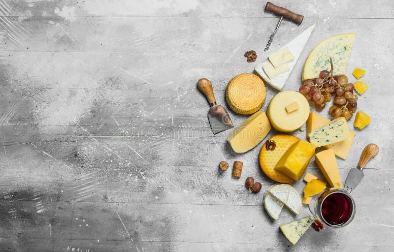 Olika typer av ost med druvor, muttrar och ett exponeringsglas av rött vin arkivbild