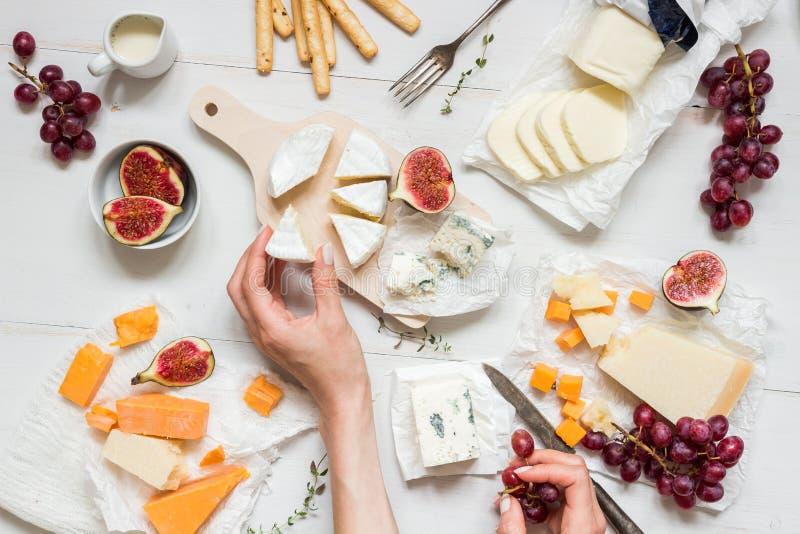 Olika typer av ost med frukter och mellanmål på den trävita tabellen Top beskådar arkivbild