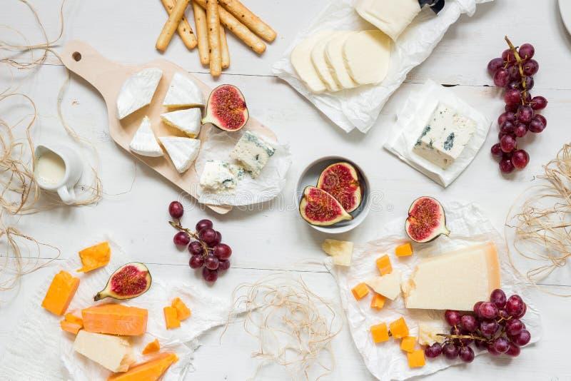 Olika typer av ost med frukter och mellanmål på den trävita tabellen Top beskådar arkivfoto