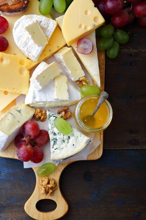 Olika typer av ost med honung, druvor, bröd och valnötter på skärbräda arkivbild