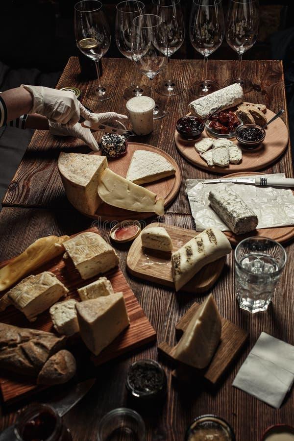 Olika typer av ost med olika kryddor och vinexponeringsglas på den tomma utrymmebakgrunden arkivbild
