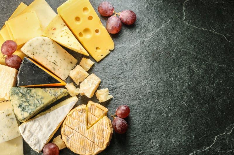 Olika typer av ost med tom utrymmebakgrund royaltyfria bilder