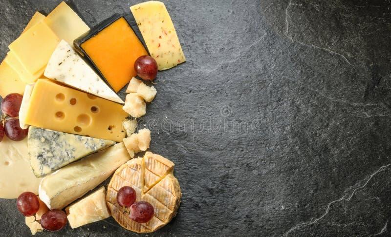 Olika typer av ost med tom utrymmebakgrund arkivbild