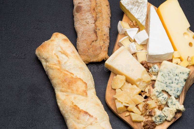 Olika typer av ost och bröd på träbräde royaltyfri bild