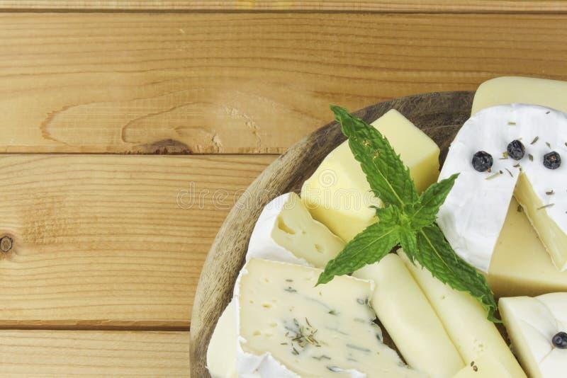 Olika typer av ost på en skärbräda arkivbilder