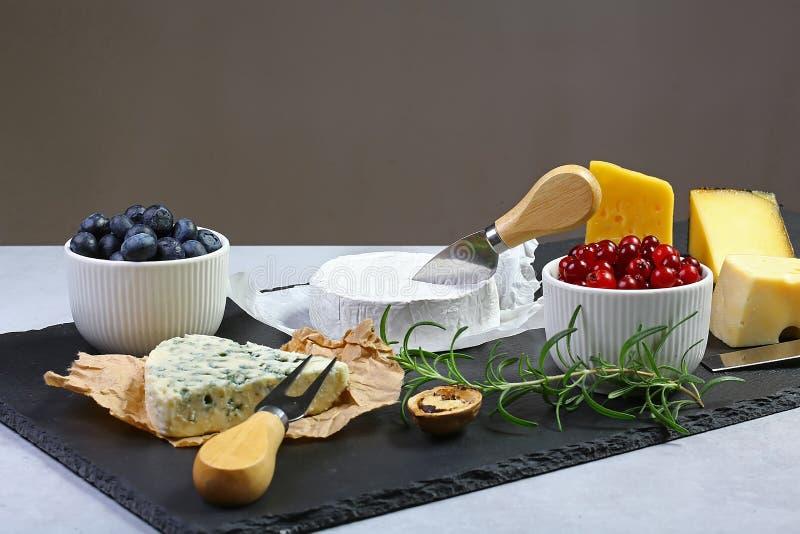 Olika typer av ost på en träbakgrund Sortiment av ost med valnötter, tranbär, rosmarinkvist, blåbär på en stenplatta Ostportionkn fotografering för bildbyråer