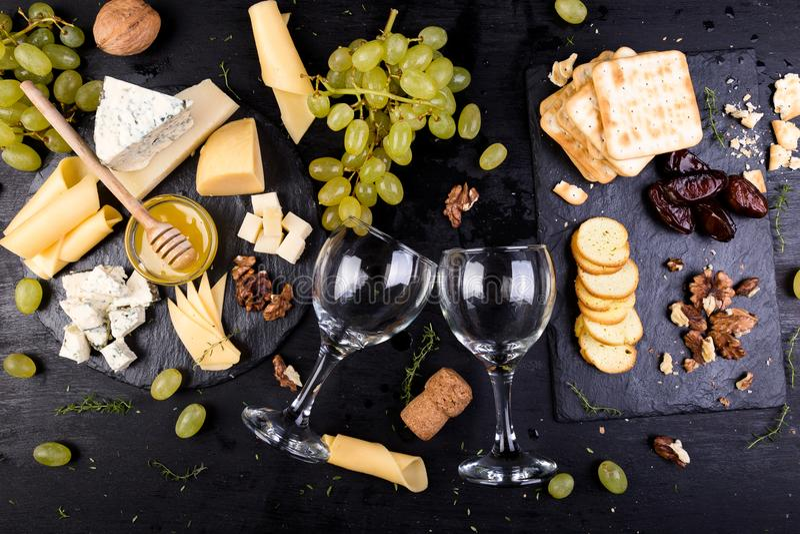 Olika typer av ost på en träbakgrund Sortimentet av ost med valnötter, panerar en honung på stenen kritiserar plattan arkivbild